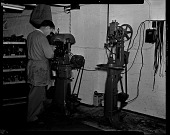 view Man in smock standing at machine working, shoe polishing machine?], Carver Shoe Repair digital asset: untitled