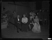 view Three women and a man in formal dress seated on folding chairs, talking and watching surroundings. Possibly from a U.S.0. (United Service Organization) function that was attended by Eleanor Roosevelt digital asset: untitled