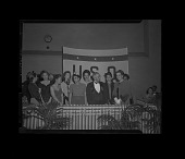 view Group of formally dressed men and women standing on a dais in front of a USO (United Service Organizations) banner digital asset: untitled