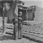 view Child standing near drying mud bricks, in Bamako, Mali digital asset: Child standing near drying mud bricks, in Bamako, Mali