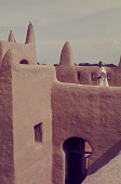 view A Muezzin standing on the wall of the Grand Mosque of San, San, Mali digital asset: A Muezzin standing on the wall of the Grand Mosque of San, San, Mali