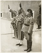 """view """"Princely Guest from Ethiopia"""": the Sultan of Gimma (left) and Italian Dictator Benito Mussolini Salute Parading Troops digital asset: """"Princely Guest from Ethiopia"""": the Sultan of Gimma (left) and Italian Dictator Benito Mussolini Salute Parading Troops"""