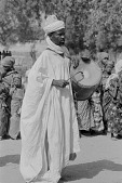 view A Hausa drummer wearing an agbada at harvest celebration, Nigeria digital asset: A Hausa drummer wearing an agbada at harvest celebration, Nigeria