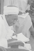 view A Hausa man in a white robe writing in a book and talking, Nigeria digital asset: A Hausa man in a white robe writing in a book and talking, Nigeria