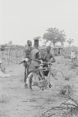 view Kamberi young men with a bicycle outside of the village, Yelwa, Nigeria digital asset: Kamberi young men with a bicycle outside of the village, Yelwa, Nigeria