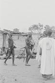 view A Kamberi man carrying farming tools in a village market, Yelwa, Nigeria digital asset: A Kamberi man carrying farming tools in a village market, Yelwa, Nigeria