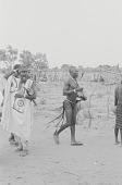 view A Kamberi man carrying farming tools through a village market, Yelwa, Nigeria digital asset: A Kamberi man carrying farming tools through a village market, Yelwa, Nigeria
