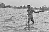 view A young boy catching fish with a long line of Kainji Reservoir, Kainji Reservoir region, Nigeria digital asset: A young boy catching fish with a long line of Kainji Reservoir, Kainji Reservoir region, Nigeria