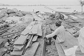 view A man carving a plank of wood to repair a dugout canoe on the shore of Kainji Reservoir, Kainji Reservoir region, Nigeria digital asset: A man carving a plank of wood to repair a dugout canoe on the shore of Kainji Reservoir, Kainji Reservoir region, Nigeria