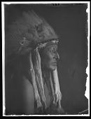 view Portrait of Crow man White Swan wearing feathered headdress. Logbook title White Swan (Custer's Chief of Indian Scouts) digital asset: Portrait of Crow man White Swan wearing feathered headdress. Logbook title White Swan (Custer's Chief of Indian Scouts)