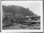 view Group, possibly Duwamish, sitting among canoes with buildings in background. Logbook title Indians in Camp digital asset: Group, possibly Duwamish, sitting among canoes with buildings in background. Logbook title Indians in Camp
