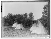 view Several Assiniboine people seated beside four tipis. Logbook title An Assiniboine Camp digital asset: Several Assiniboine people seated beside four tipis. Logbook title An Assiniboine Camp