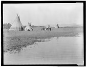 view Assiniboin camp at edge of lake showing several people and tipis digital asset: Assiniboin camp at edge of lake showing several people and tipis