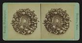 view [Funerary floral arrangement]: portrait in wreath. digital asset: [Funerary floral arrangement]: portrait in wreath.