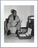 view Photographic print of Dizzy Gillespie seated next to an open instrument case digital asset number 1