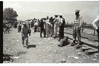 view Braceros on Railroad Tracks digital asset: Braceros stand beside railroad tracks while waiting to enter the Monterrey Processing Center, Mexico.