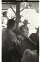 view Reviewing Braceros' Documents digital asset: Braceros wait in line and present their documents to an official standing in a wooden shed at the Monterrey Processing Center, Mexico.