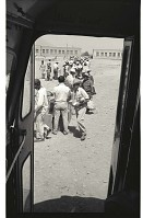 view Braceros Boarding Buses digital asset: Framed by a bus door, braceros recieve packed lunches as they board buses from Monterrey Processing Center, Mexico, to the Hidalgo Processing Center, Texas, on the U.S.-Mexico border.