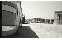 view Braceros Boarding Buses digital asset: Framed by the side of a bus at the Monterrey Processing Center, Mexico, braceros board buses to the Hidalgo Processing Center, Texas, on the U.S.-Mexico border.