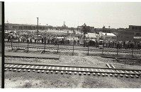 view Braceros Waiting at Processing Center digital asset: Beyond railroad tracks, a large group of braceros waits for processing at the Monterrey Processing Center, Mexico.