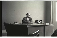 view Official in Mexico City digital asset: Eugenio de Azorena sits behind his desk and speaks to someone while smoking in his office, Mexico City, Mexico.