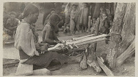view Two Women in Costume Weaving on Back-Strap Looms Attached To Tree Stumps; Group Watching Nearby n.d digital asset number 1