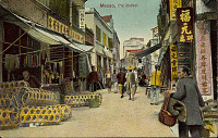view View of Commercial Street Showing Group in Costume, Storefronts, and Pig Market with Baskets of Pigs Outside n.d digital asset number 1