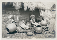 view Two Old Women with Large Ceramic Containers Outside Thatched House 1936 digital asset number 1