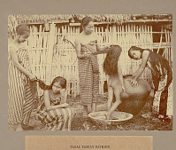 view Three Women and Girl Taking Bath Outside Wooden Bamboo House with Thatch Roof 1901 digital asset number 1