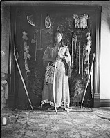 view Woman wearing dress with bead or quill work holding bow and arrow and standing in front of a display of Native American objects digital asset: Woman wearing dress with bead or quill work holding bow and arrow and standing in front of a display of Native American objects
