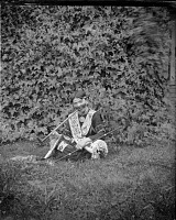 view Boy (not Native American) wearing Native American regalia including medal with pipe in mouth digital asset: Boy (not Native American) wearing Native American regalia including medal with pipe in mouth