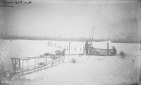 view Two Men in Native Dress, with Sled and Dog Team, Setting Up Fish Trap on Ice 1879 digital asset number 1