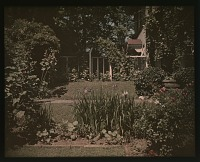 view [Unidentified Garden in Unidentified Location]: house with flower bed, arbor, lattice and gate. digital asset: [Unidentified Garden in Unidentified Location] [lantern slide]: house with flower bed, arbor, lattice and gate.