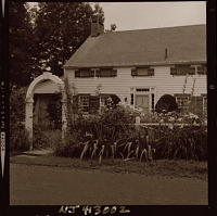 view [Unidentified Garden in Mendham, New Jersey [on Corey Lane]]: house, arbor, and daylily border. digital asset: [Unidentified Garden in Mendham, New Jersey [on Corey Lane]] [safety film negative]: house, arbor, and daylily border.