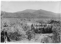 view Unidentified Landscape: an unidentified location in either the White Mountains of New Hampshire or the Adirondack Mountains of New York, with a railroad line and buildings in the center of the image and a small river in the foreground. digital asset: Unidentified Landscape [glass negative]: an unidentified location in either the White Mountains of New Hampshire or the Adirondack Mountains of New York, with a railroad line and buildings in the center of the image and a small river in the foreground.