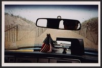 Photo shows the dashboard and windshield of de Land's car, parked at the beach at Cape Cod, Massachusetts. De Land is visible in the rear view mirror. On the dashboard is a snapshot of Pat Hearn and two small American flags.  Stamp on verso indicates photo was developed September 16, 2000. Photograph most likely taken after Pat Hearn's death on August 18, 2000.
