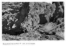Rockshelter lies at base of cliff, above stream.