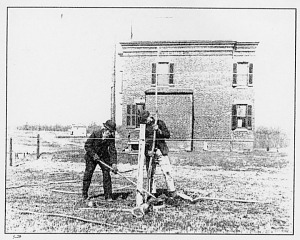 Grandfather and grandson raise a fence in the mostly undeveloped suburb of Columbia Heights, about 1904