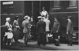 A conductor (middle left) and porter (second from right) assist travelers boarding a passenger train.