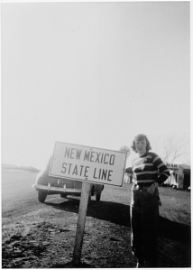 Janet McDonnel with road sign on Route 66 at New Mexico state line.