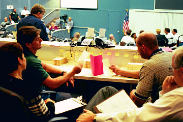 Citizen ballot counters and observers examining Votomatic punch cards, Emergency Operations Center, West Palm Beach, Florida, November 2000