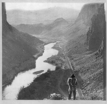 Native American man (Shoshone) looking at the Central Pacific Railroad, about 1869