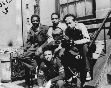 Stickball players sit on a stoop ready for the next game, East Harlem, New York, 1961