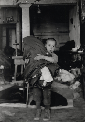 Italian boy holding a bundle of cloth, New York City, around 1910