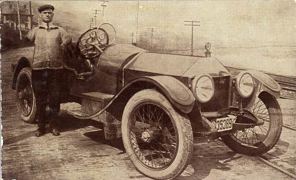 Postcard of Frank Fithen, showing him alongside his vehicle adapted for armless driving