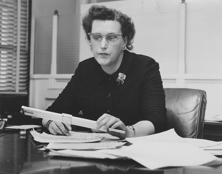 Engineer Catherine Eiden using a slide rule to make calculations, 1960s