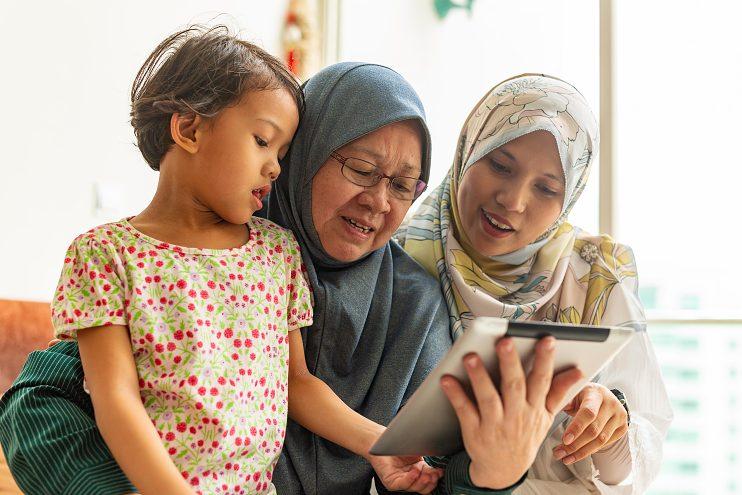 Family looking at iPad, around 2018