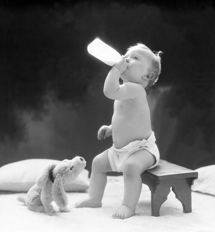 A child drinking milk out of the bottle, 1930s