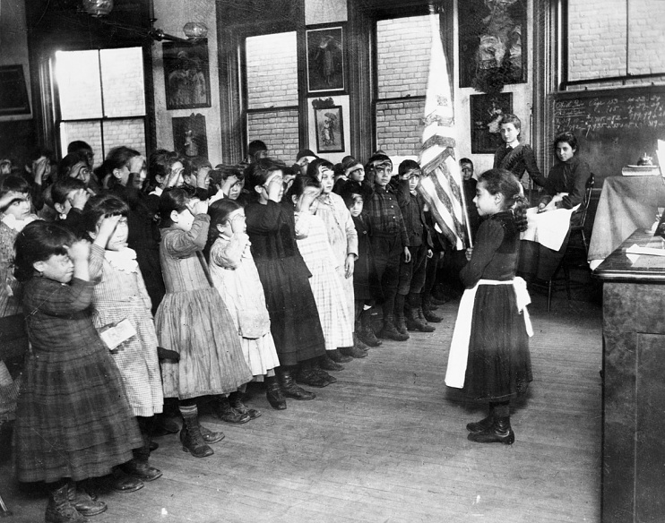 Photograph by Jacob Riis of students in Mott Street Industrial School saluting the flag, New York City, around 1892