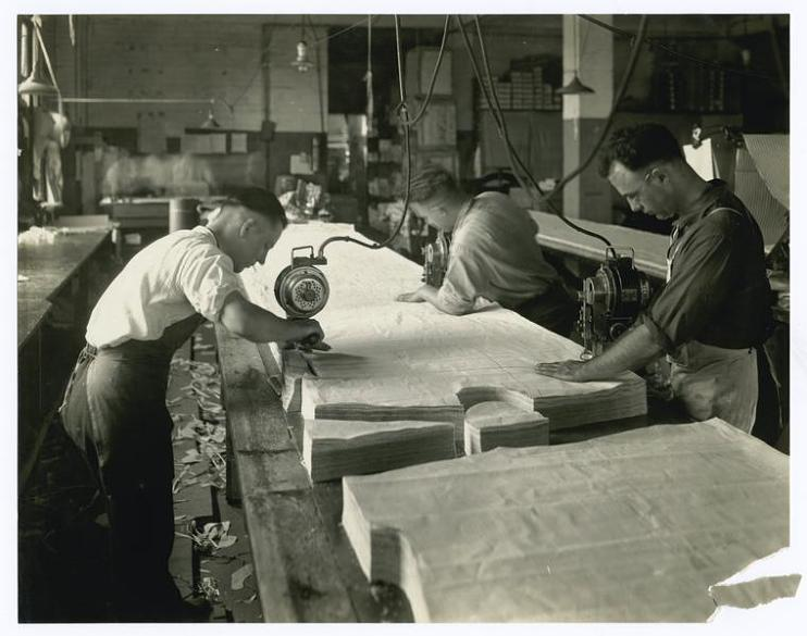 Cutting stacks of fabric, about 1920